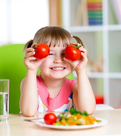 Child with tomatoes. Happy little girl with healthy meal and vegetables at school